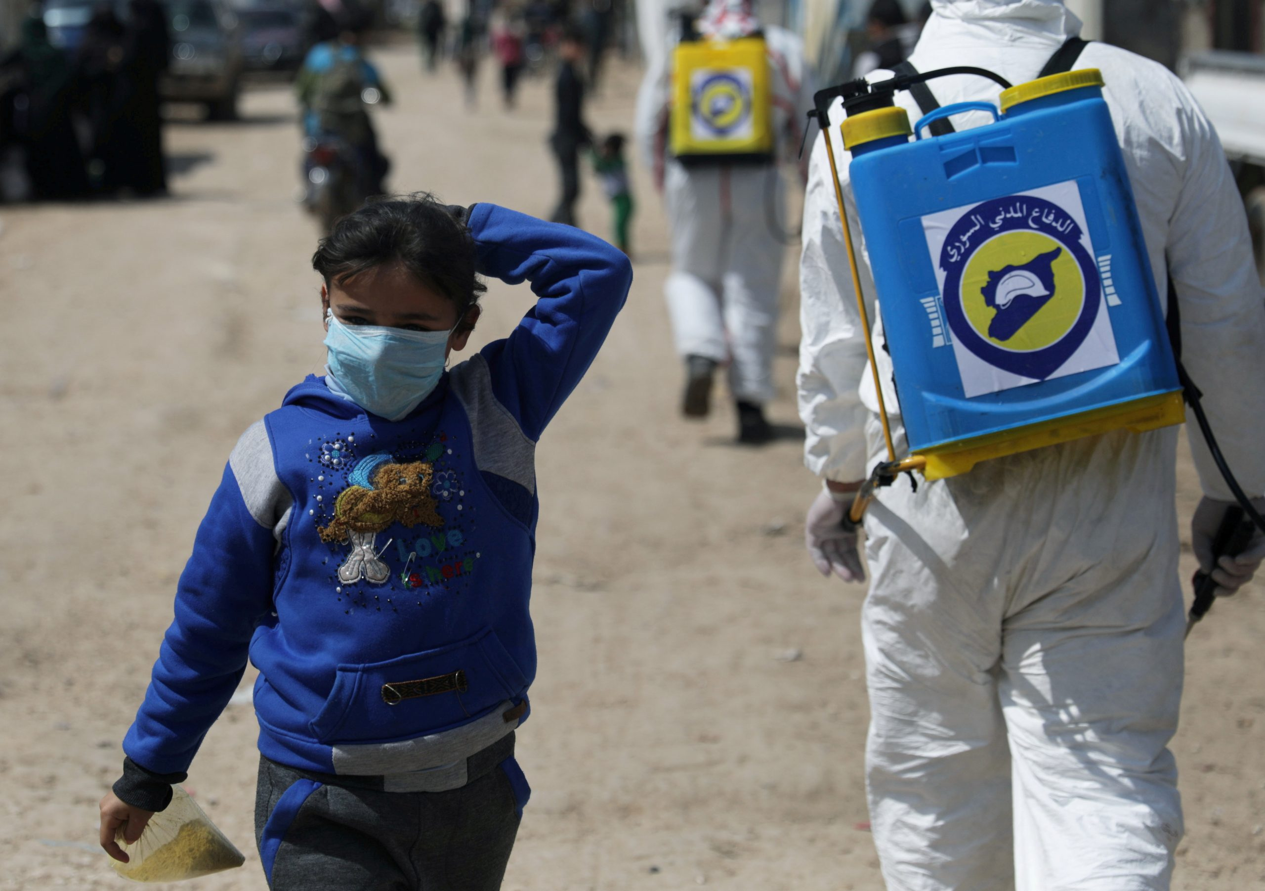 An internally displaced Syrian girl wears a face mask as members of the Syrian Civil defence sanitize the Bab Al-Nour internally displaced persons camp, to prevent the spread of coronavirus disease (COVID-19) in Azaz, Syria. (Khalil Ashawi, March 26th, 2020) Reuters.