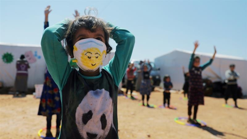 A displaced girl wears a face mask as she takes part in an event organized by Violet Organization, in an effort to spread awareness and encourage safety amid coronavirus disease (COVID-19) fears, at a camp in the town of Maarat Masrin in northern Idlib, Syria. (Khalil Ashawi, April 14th, 2020) Reuters.