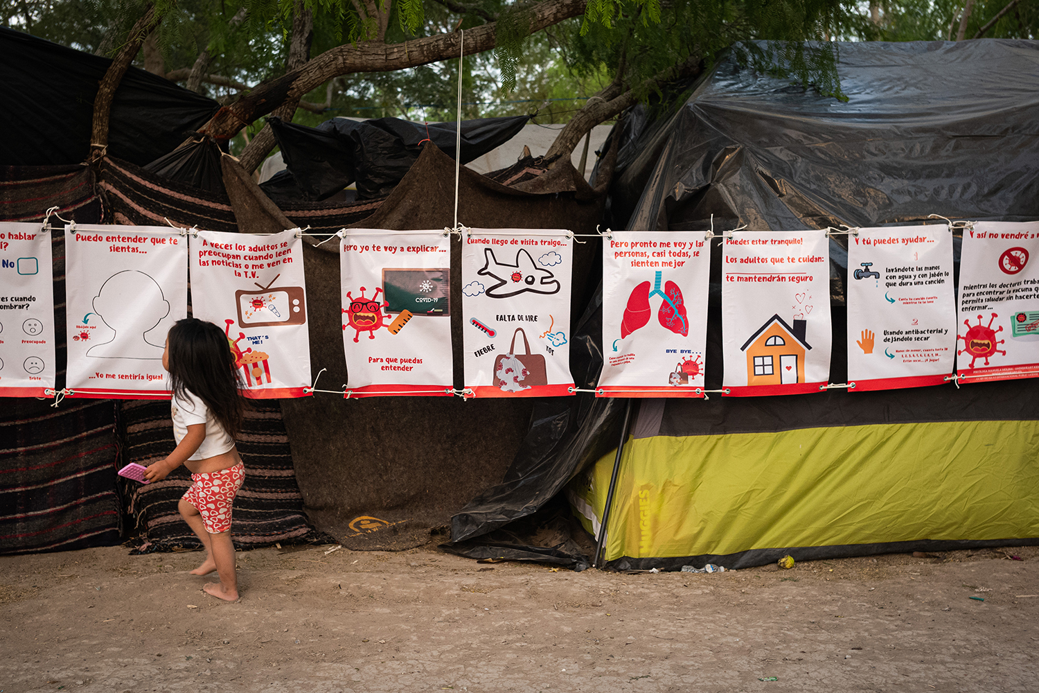 A girl runs past a series of signs explaining how the coronavirus spreads at the Matamoros refugee camp on March 19. (Ivan Flores, March 19th, 2020) Foreign Policy.