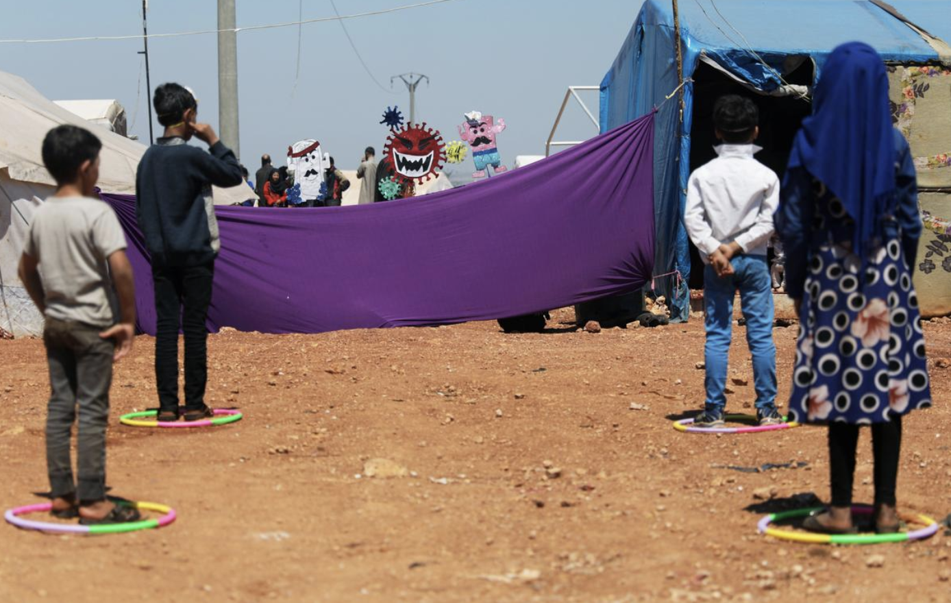 Displaced children attend a puppet show during an event organzied by Violet Organization, in an effort to spread awareness and encourage safety amid coronavirus disease (COVID-19) fears, at a camp in the town of Maarat Masrin in northern Idlib, Syria (Khalil Ashawi, April 14th, 2020) Reuters.