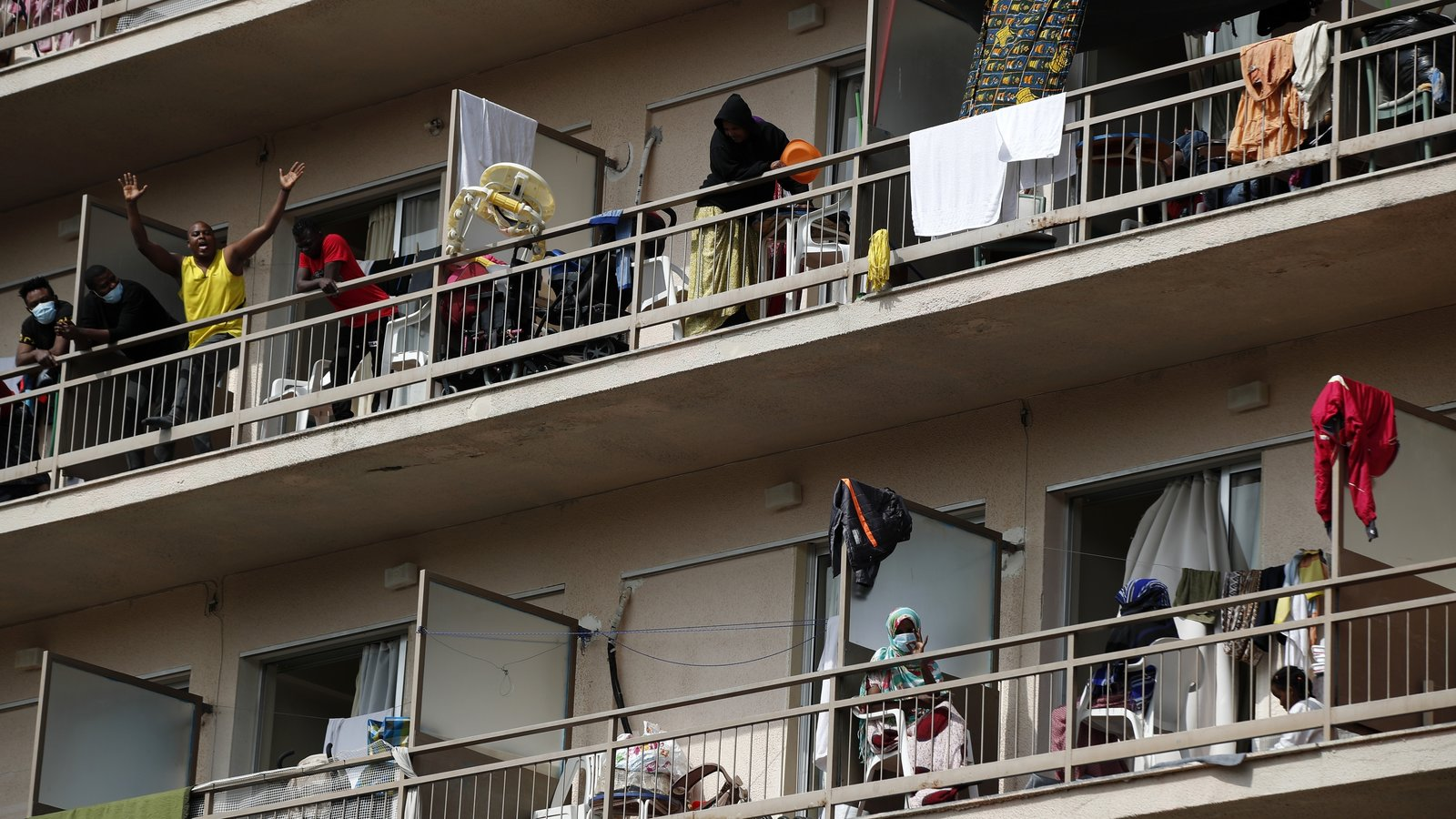 Migrants wave from their balconies in Kranidi, southern Greece, on Tuesday. Authorities confirmed a high number of COVID-19 infections at the site. (Thanassis Stavrakis, N/A) AP.