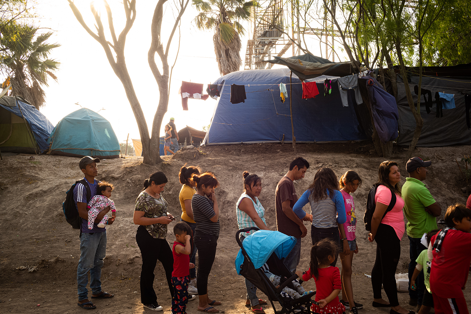 Migrants wait in line for food distribution at the Matamoros camp on March 19. Food was previously given out in a centralized tent but is now distributed at separate locations in the camp to prevent large gatherings. (Ivan Flores, March 19th, 2020) Foreign Policy.