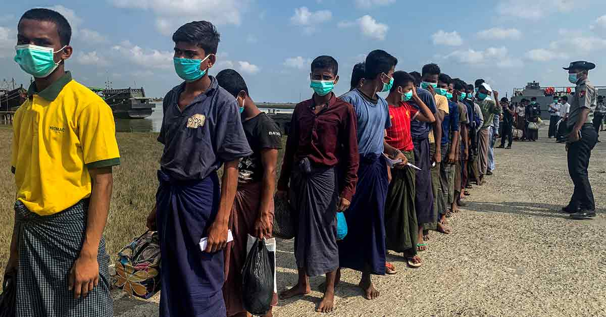 Released Rohingya prisoners wearing face masks amid concerns of the COVID-19 coronavirus pandemic arrive in Sittwe jetty in Rakhine State after being transported by military boat on April 20, 2020. - Myanmar sent more than 800 Rohingya back to its restive Rakhine state April 20 after releasing them from various overcrowded jails as the country, accused of genocide against the minority, tries to grapple with the coronavirus crisis. (N/A, April 20th, 2020) Getty Images.